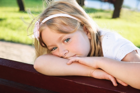 runaway: child problem  sad little girl 6 years old sitting at the park Stock Photo