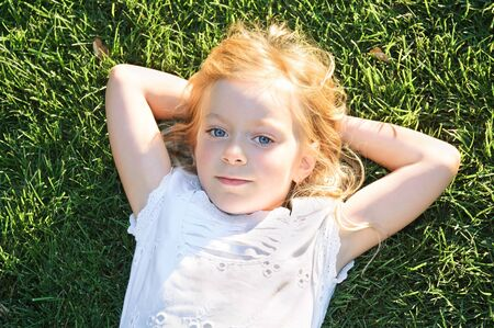 portrait of  little girl relaxing on green grass