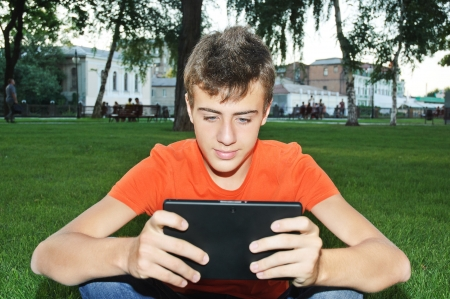 teenager boy having fun with tablet pc at park