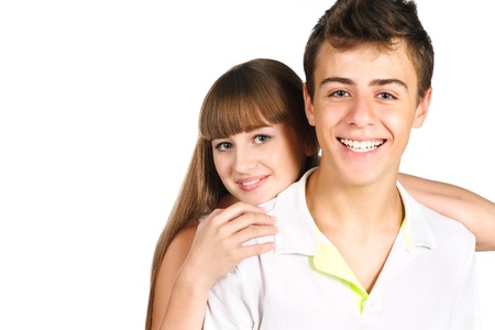 Smiling teenager boy with his beautiful girlfriend on his back isolated over white Stock Photo
