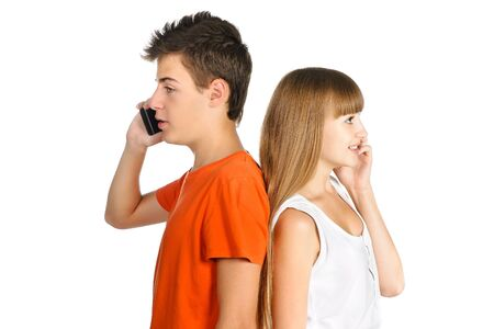 teenage boy and girl chatting on cell phones standing back to each other isolated over white Stock Photo