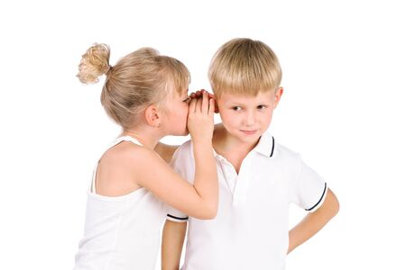 tells: 5-7 years old girl tells a secret to the boyfriend  isolated over white background