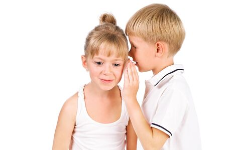 tells: 5-7 years old boy tells a secret to the girl isolated over white background