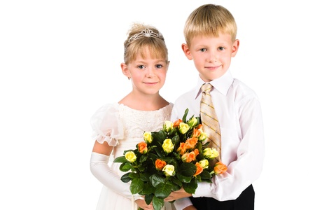 innocense: portrait of beautiful boy and girl holding flowers isolated over white