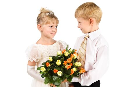innocense: The first love concept  Beautiful couple of kids wearing formal attire owers isolated over white
