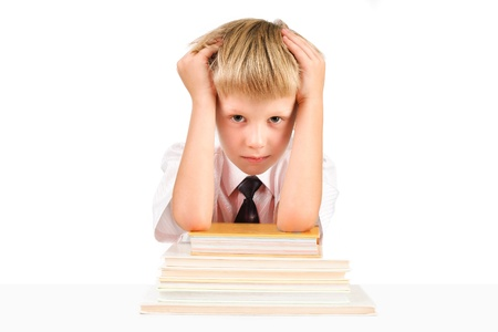 Tired little schoolboy sitting at a table with books isolated on a white background