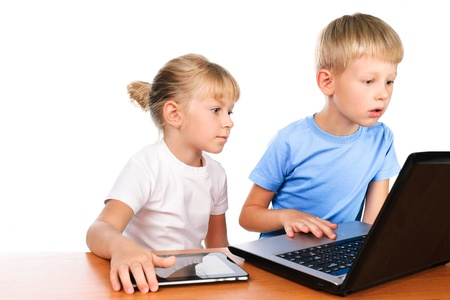 elementary boy and girl sitting at table using digital pad and laptop Stock Photo