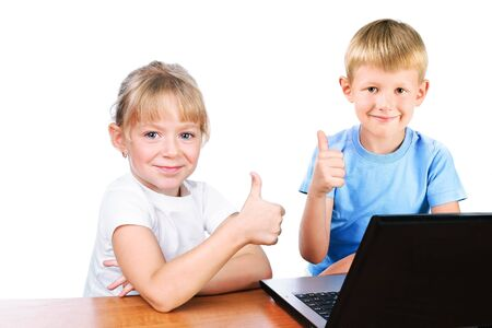 happy girl and boy behind laptop with thump up sign isolated over white Stock Photo