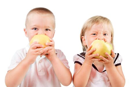 two kids eating yellow apples isolated over white