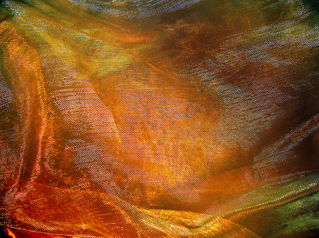 draped: Golden background from transparent fabric mesh