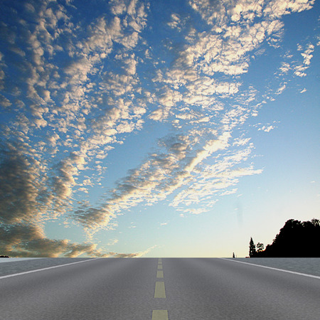 Landscape with road, silhouettes of trees and white clouds. Highway with dramatic sky, fluffy clouds and trees Фото со стока