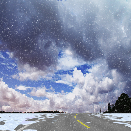 Winter panoramic landscape with road, silhouettes of trees, flying snow and clouds. White, gray and blue dramatic sky and highway with snow drifts