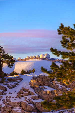 Large white domes of the weather station on the mountain against the backdrop of a colorful evening sky in the clouds.