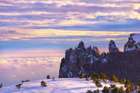 Sharp mountain peaks above fabulous multi-colored clouds. Unreal beautiful winter landscape. Snowy plain with snowy pine trees and trees. Banco de Imagens