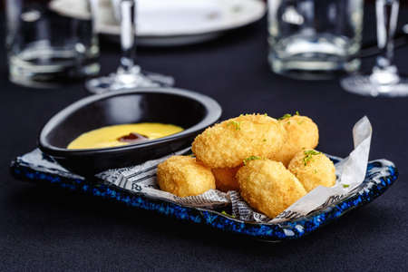 Fried mozzarella cheese sticks with cheese sauce and lime zest