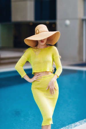Beautiful woman in big hat posing next to the pool.
