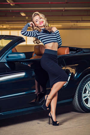 Une fille de style pin up s'assoit dans la voiture Banque d'images - 81569578