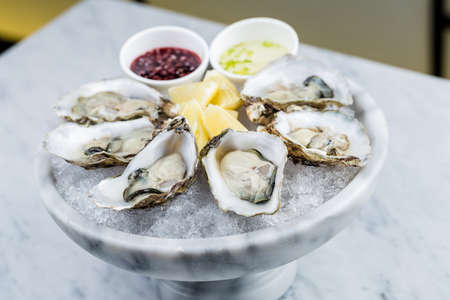 Fresh oysters platter with sauce and lemon served on a marble vase with ice. Stock Photo