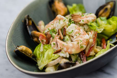 napkin ring: Seafood salad with shrimps, calamari and mussels on marbel desk.