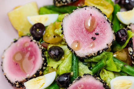 Raw and fresh tuna meat with sesame and fresh vegetable salad on marbel desks. Stock Photo
