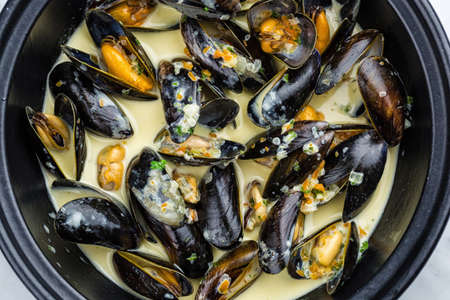 metalic: Soup of mussels creamy in black bowl on marbel surface. Stock Photo