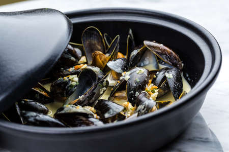 Soup of mussels creamy in black bowl on marbel surface. Stock Photo