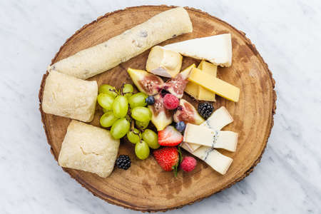 roquefort: Cheese plate with bread grapes and strawberries in a wooden desk on marble surface.