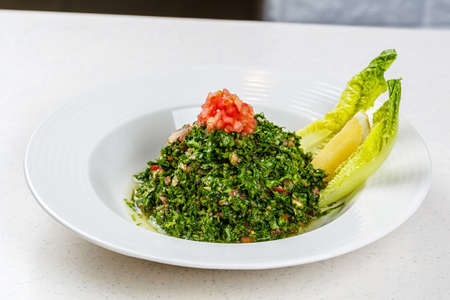 Arabic traditional salad Tabbouleh with Fresh Parsley, Tomatoes, Cracked Wheat, Onions, Freshly Squeezed Lemon Juice Virgin Olive Oil. Stock Photo