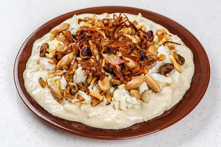 Hummus with olive oil and nuts on the brown plate
