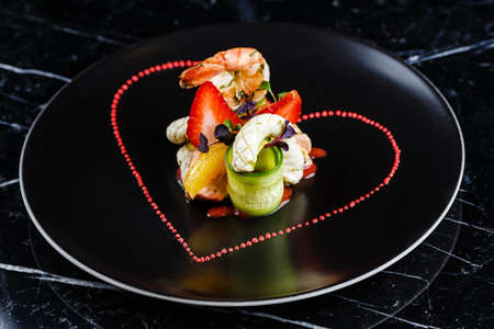 Grilled prawns and calamari appetizer with fruits and slices of cucumber served on the black plate with the black background Stock Photo