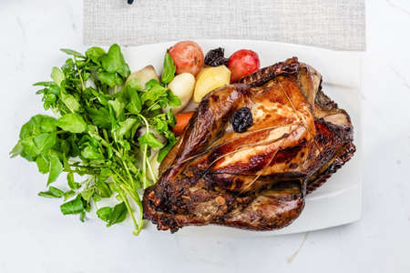 Garnished roasted turkey on platter on marble surface Stock Photo