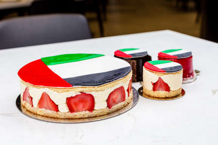 UAE National holiday celebration flag print cake and cupcakes on marble table