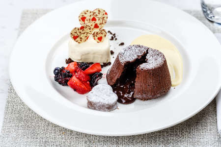 Chocolate fondant lava cake with ice cream strawberries and berries on white plate on marble serface