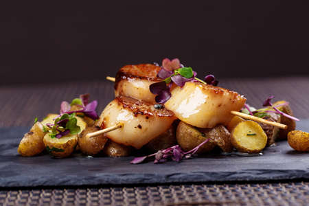 Grilled scallops with roasted young potatoes Archivio Fotografico