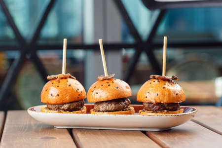 Small burgers served on one plate as appetizers and decorated with truffles