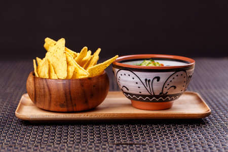 mexico - guacamole and nachos in bowl on wooden plate