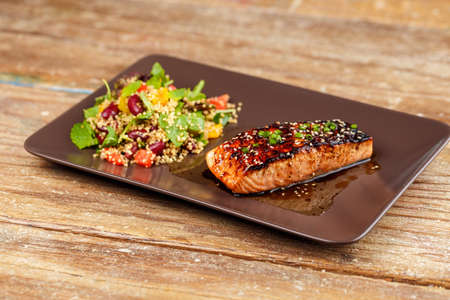 brown trout: Grilled salmon with quinoa salad on brown plate.