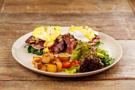 Hamburger , burger with grilled beef, egg, cheese, bacon and vegetables in white plate on wooden serface. Stock Photo