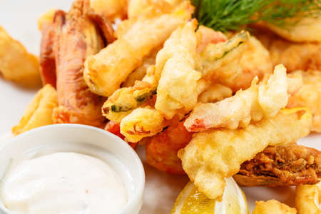 creole: Breaded Prawns - King prawns coated in plain and spicy breadcrumbs and deep-fried on white plate with full serving.