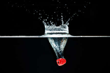 Raspberry falls deeply under water with a big splash on black backdrop