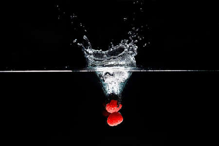 Two raspberrys falls deeply under water with a big splash.