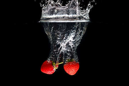 Two strawberrys splashing into water Stock Photo