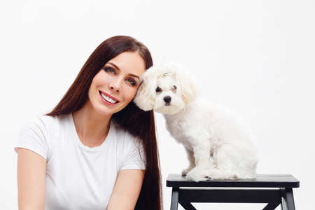 Beautiful brunette girl with long hair sits next to white Maltese puppy and smiling with the teeth
