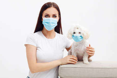 Girl wears disposable mask hugs her puppy. Dog wears disposable mask too