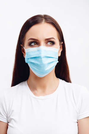 Brunette woman wearing disposable mask shows emotions with her eyes Stok Fotoğraf