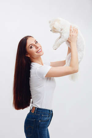 Beautiful brunette girl smiling with the teeth, holds white Maltese puppy and her hair flies