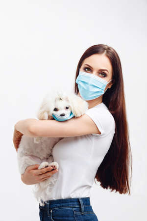 Girl wears disposable mask holds her puppy wears disposable mask too