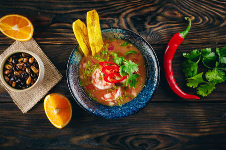 Prawn ceviche served on the wooden table with chilli pepper