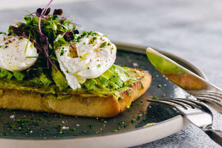 Guacamole and poached egg bruschetta served with greens and sliced avocado