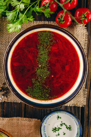 Red borsch served on the linen napkin surrounded with vegetables